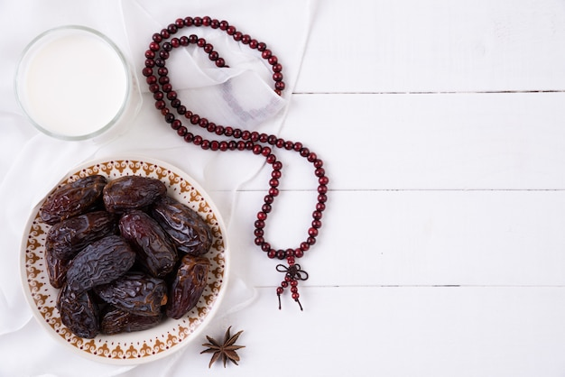 라마단 음식과 음료 개념입니다. 나무 묵주, 우유 및 날짜 과일