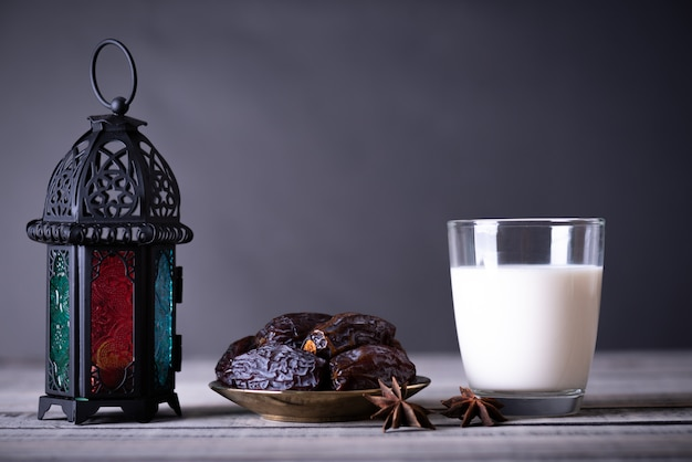 Ramadan food and drinks concept. ramadan lantern with milk, dates fruit