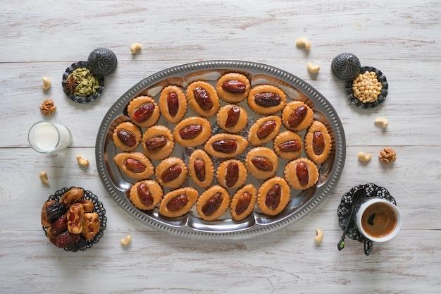 ラマダン食品テーブル。白い木製のテーブルにイードデートのお菓子