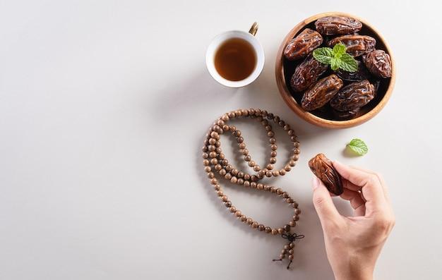 ラマダンカリームの背景、ナツメヤシ、お茶、ロザリオビーズを拾う手。