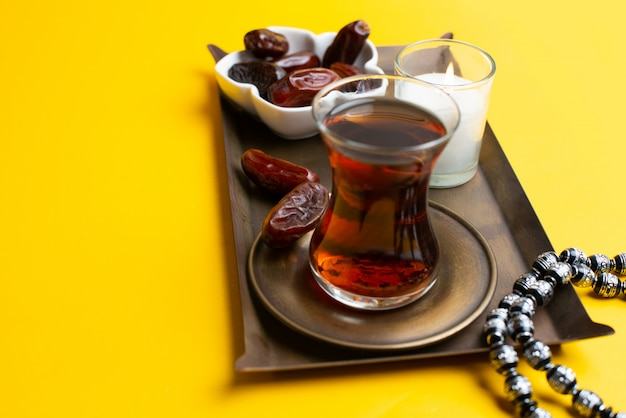 Ramadan kareem festival, close up of dates at bowl with rosary and cup of black tea