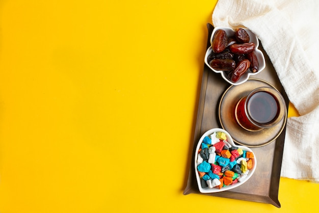 Ramadan kareem festival, dates on bowl with cup of black tea and colorful candies