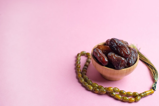 Ramadan kareem festival, dates at bowl with rosary on pink background