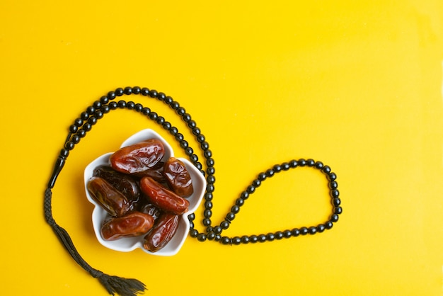 Ramadan kareem festival, dates at bowl with rosary on yellow background