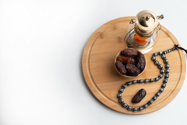 Ramadan kareem festival, dates on wooden bowl with candle lamp and rosary