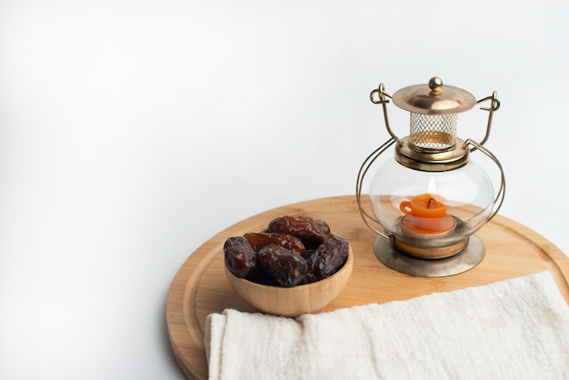 Ramadan kareem festival, dates on wooden bowl with candle lamp