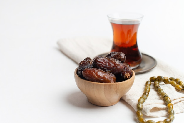 Ramadan kareem festival, dates on wooden bowl with cup of black tea and rosary