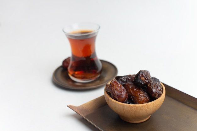 Ramadan kareem festival, dates at wooden bowl with cup of black tea on white isolated background
