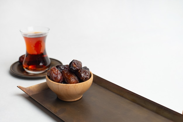 Ramadan kareem festival, dates at wooden bowl with cup of black tea