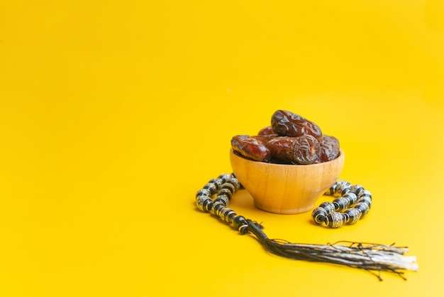 Ramadan kareem festival, dates at wooden bowl with rosary on yellow background