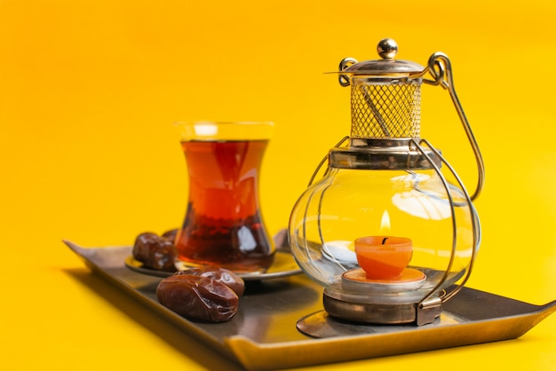 Ramadan kareem festive, close up of dates on plate with oriental candle lamp and cup of black tea