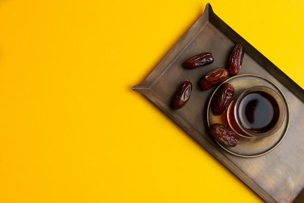 Ramadan kareem festive, dates on plate and cup of black tea