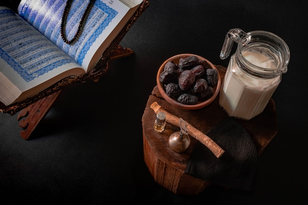 Ramadan kareem mubarak islamic dark surface with quran, dates, milk, miswak, itar and antimony, copy space