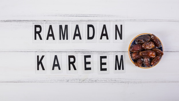 Ramadan kareem text with bowl of juicy dates on white desk