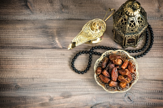 Ramadan lamp, rosary and dates on wooden background. festive still life with oriental lantern. vintage style toned picture with vignette