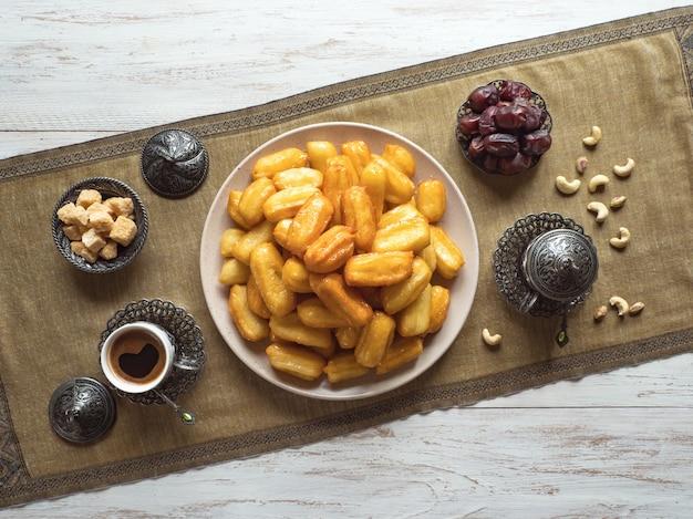 Рамадан сладости. печенье эль фитр исламский праздник. тулумба - пропитанный арабским сиропом жареный губчатый мед.