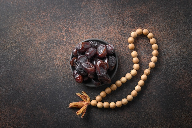 Ramadan wooden prayer beads and dates in bowl on brown eid mubarak religious tradition