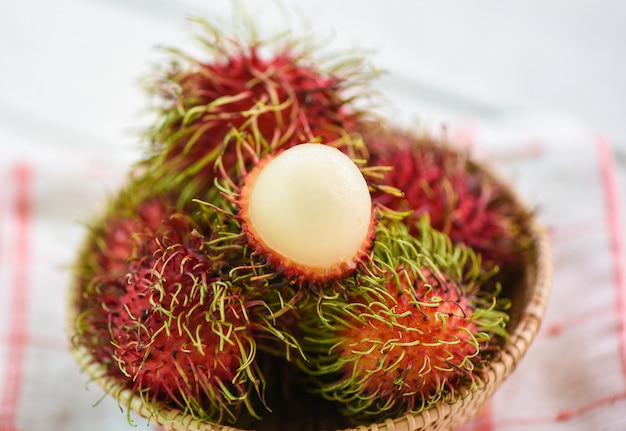 Rambutan peeled in a basket on table - fresh rambutan summer fruit from garden in thailand