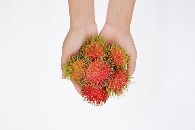 白い背景にrambutans果物を保持する手。