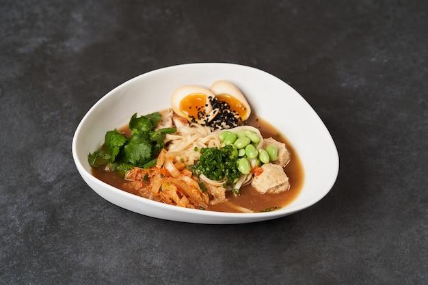 Суп с лапшой рамэн с курицей, грибами шиитаке и яйцом в белой миске, вид сверху