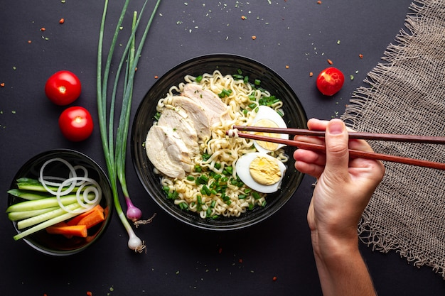 Ramen noodles black bowl with chicken, vegetables, chives and egg on black background top view.
