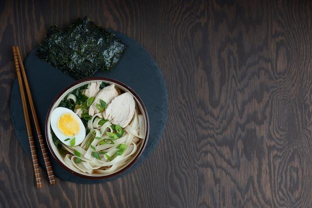 木製のテーブルに箸を入れたボウルに鶏肉、麺、ゆで卵を入れたラーメンスープ