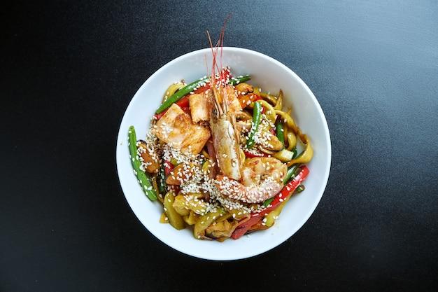 ムール貝、エビ、野菜を黒の白いボウルに中華なべで炒めたラーメン。セレクティブフォーカス。閉じる。おいしい屋台の食べ物。シーフード