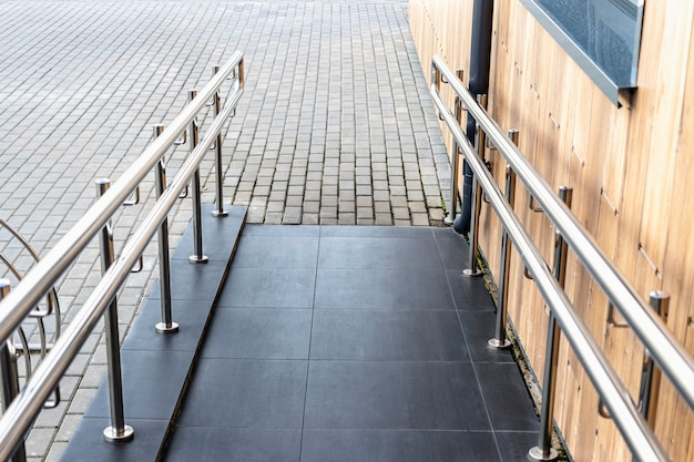 A ramp and metal railings at the entrance to the residential building for the convenience of disabled and elderly people.