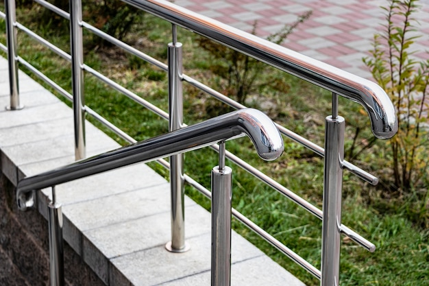 A ramp and metal railings at the entrance to the residential building for the convenience of people with disabilities and the elderly.