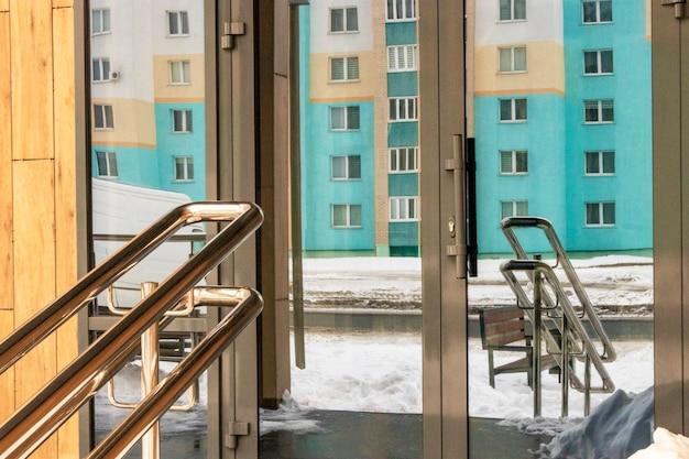 건물 진입로 앞에 휠체어 장애인을 위한 스테인리스 스틸 난간이 있는 경사로.