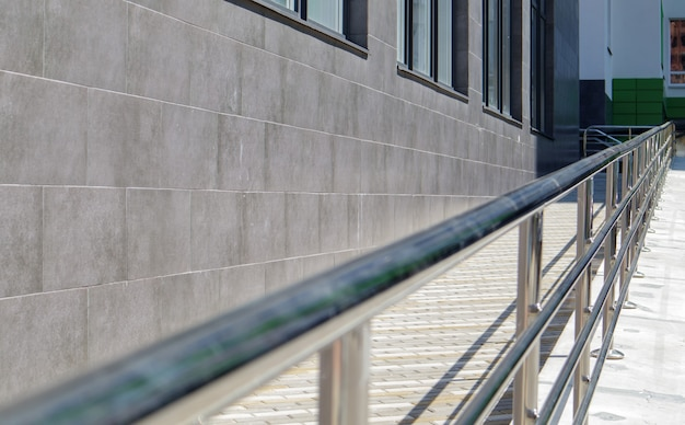 A ramp with stainless steel handrails for wheelchairs, bicycles and strollers with children in front of the building. handrail for lifting a wheelchair. shiny stainless steel handrail.