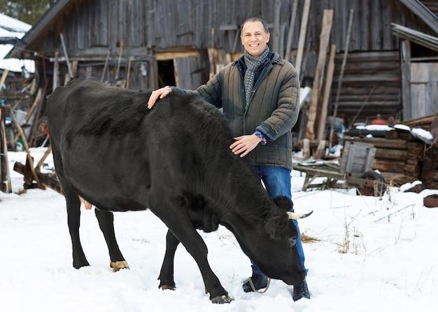 Владелец ранчо в повседневной зимней одежде стоит с коровой в сельской местности