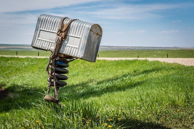 A ranchers old metal mailbox with a bridle wrapped around it in rural saskatchewan, canada