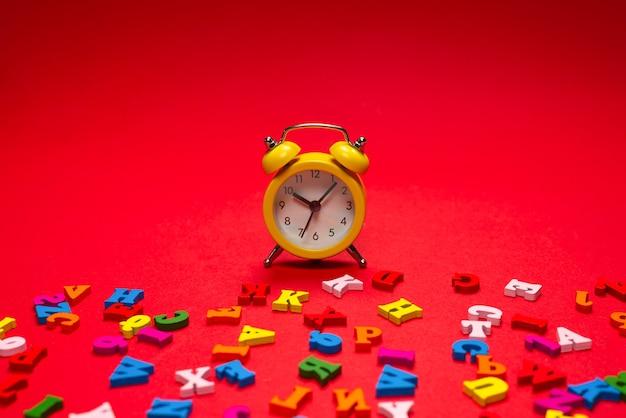 ランダムなカラフルなアルファベットと赤い背景、カラフルな文字の黄色の目覚まし時計。学校への時間。勉強の時間。教育時間。