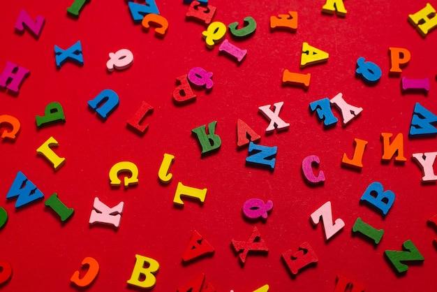 赤い背景、カラフルな文字のランダムなカラフルなアルファベット。上面図。