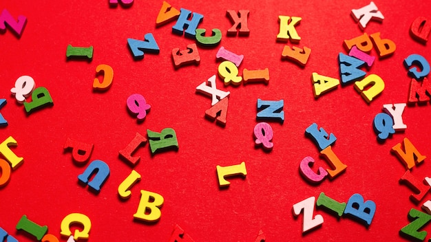 Random colorful alphabet on a red background, colorful letters. top view.