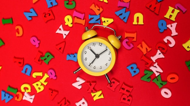 Random colorful alphabet and yellow alarm clock on a red background, colorful letters. time to school. study time. education time.