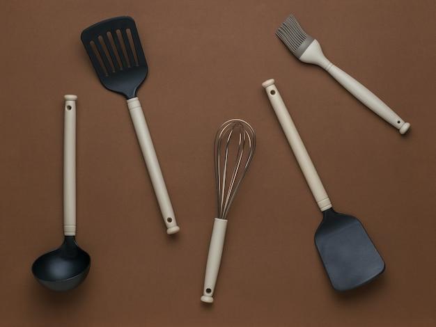 Случайно разбросанные кухонные принадлежности на коричневом фоне. плоская планировка.