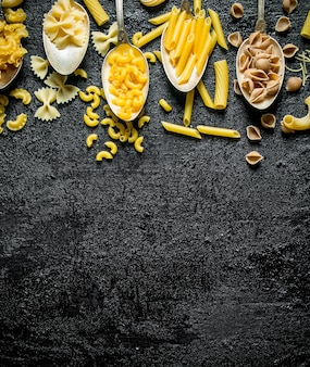 The range of different types of dry pasta in spoons