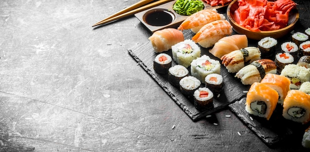 The range of different types of japanese sushi and rolls. on dark rustic background