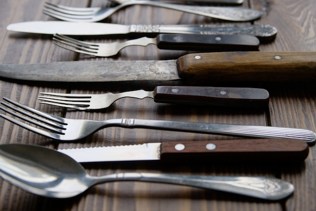 A range of different vintage cutlery with knives, forks and spoons