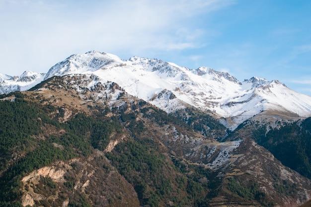 Gamma di alte montagne rocciose coperte di neve sotto il cielo nuvoloso