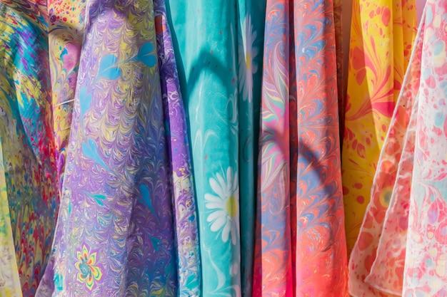 Ассортимент разноцветных шелковых шарфов в магазине.