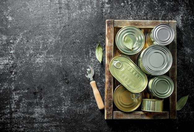 캔 따개가있는 트레이에 통조림 식품이 들어있는 다양한 밀폐 캔. 어두운 소박한 배경에