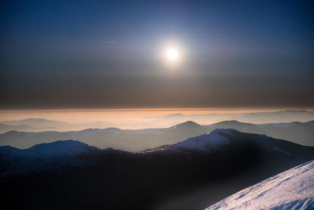 月と星と紺碧の空の下で夜の白い雪の冬の山々の範囲