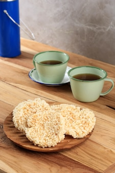 Ranginang, rangginang, or rengginang is one indonesian traditional cracker made from rice (glutinous rice) and frying. served on wooden plate, wooden table