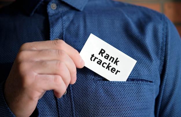 Текст трекера ранга на белом знаке в руке человека в рубашке