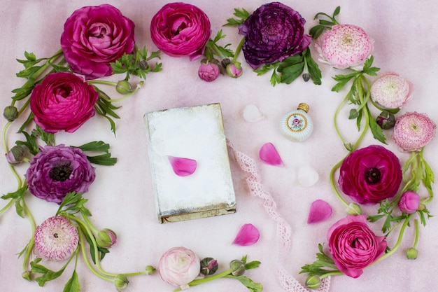 A ranunculus and a book, a bottle of perfume