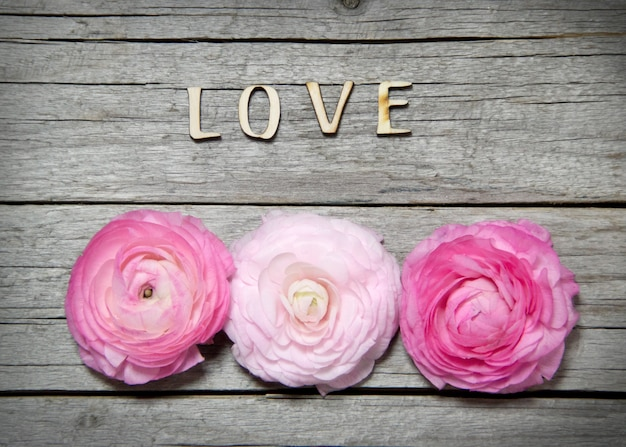Ranunculus flowers and text love on an old grey wooden table top view