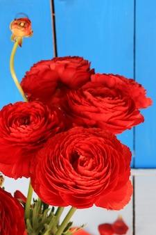 나무 배경에 붉은 꽃의 ranunkulyus 꽃다발